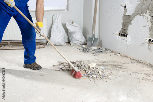 Fotografía  Manual worker sweeping rough rubble at construction site using broom