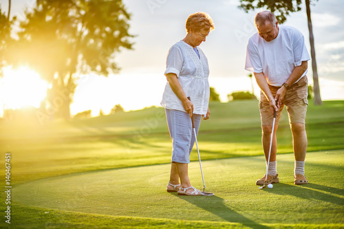 Cuadros en Lienzo  active senior lifestyle, elderly couple playing golf together at sunset