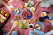 canvas print picture - Picnic blanket with healthy food and human hands with drinks over it