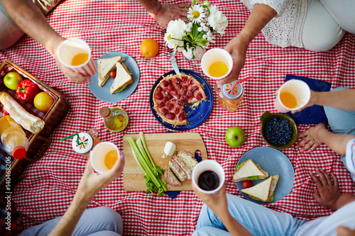 Foto Picnic blanket with healthy food and human hands with drinks over it