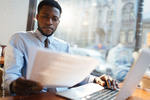 Serious employer reading resumes of candidates for vacancy Canvas Print