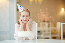 Portrait Of Sad  Lonely Mature Woman Sitting Alone At Birthday Table With Cake , Wearing Party Hat And Looking At Camera