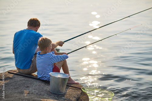 Printed kitchen splashbacks Fishing Back view portrait of adult man and teenage boy sitting together fishing with rods in calm glittering waters of blue lake on sunny summer day