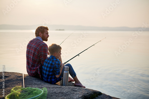 Poster de jardin Peche Back view portrait of adult man and teenage boy sitting together on rocks fishing with rods in calm waters of blue lake at dusk, both wearing checkered shirts
