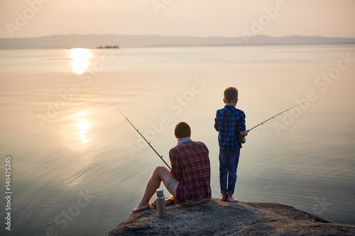 Poster Peche Back view portrait of adult man and teenage boy sitting together on rocks fishing with rods in calm waters with landscape of setting sun, both wearing checkered shirts