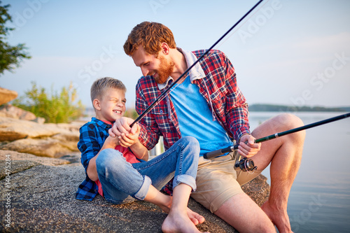 Printed kitchen splashbacks Fishing Portrait of playful handsome father tickling son sitting on rock by lake while enjoying fishing together and laughing in rays of sunset sunlight