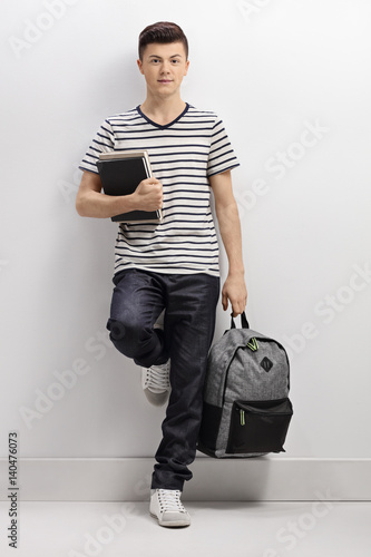Fotografía  Teenage student leaning against a gray wall