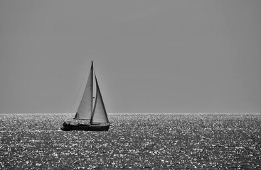 Obraz na Szkleminimalistic black and white photo of a sailing boat on a sunny day