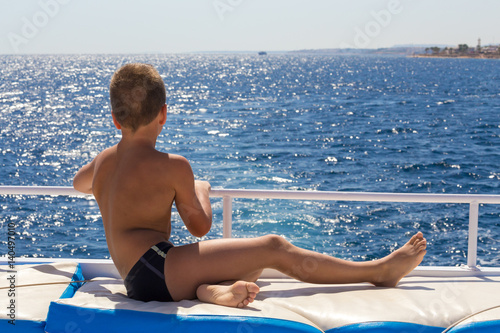 Fotografie, Obraz  Tanned boy looking to the blue sea from yacht board