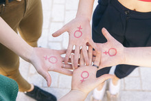 Close Up Of Small Group Of Women With The Symbol Of Feminism Written On Her Hands