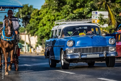 Wall Murals Old cars Blau weißer Oldtimer mit einer Pferdekutsche in Varadero Kuba - Serie Kuba Reportage