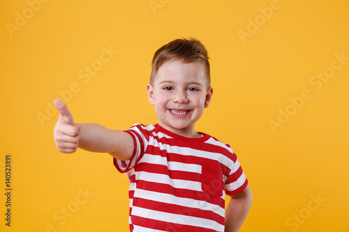 Portrait of a smiling little boy showing thumbs up Canvas Print