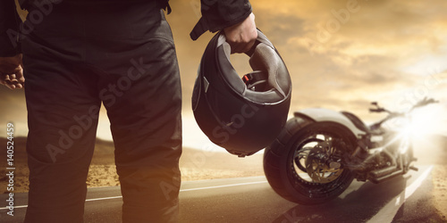 Plakat Motocyklista stoi z motocyklem na drodze
