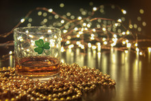 Irish Whiskey St Patricks Clover. Irish Whiskey In A Glass With A Clover Symbol, On A Pub Table With Gold Beads And Bar Lights.