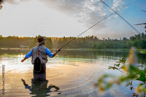 Fotografie, Tablou Young man flyfishing at sunrise