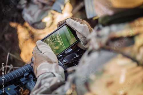 Fototapeta soldiers holding gps in hand and determines the location of coordinates