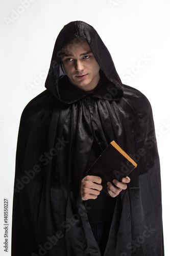 Portrait of a brutal man in a black robe with a book in their hands Canvas Print