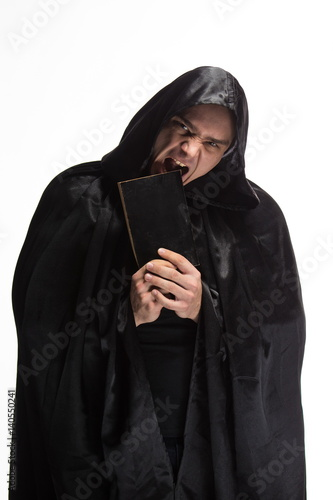 Photo Portrait of a brutal man in a black robe with a book in their hands