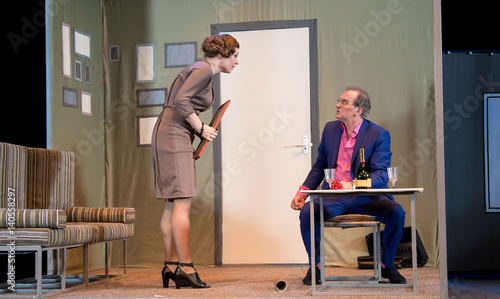 Photo Two actors, brunette woman in a brown dress and a man in a pink shirt and blue s