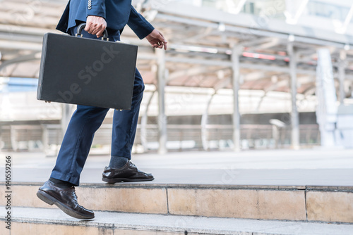 Foto  Close up shot of businessman holding leather briefcase while walking upward on the stair outdoor in city