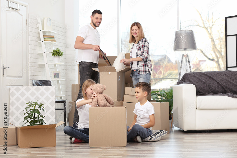 Fototapety, obrazy: House move concept. Family unpacking cardboard boxes in new home
