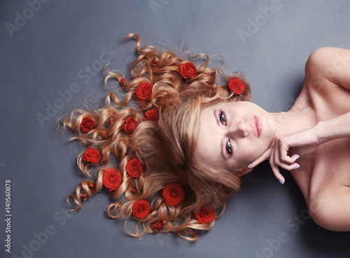 piekna-mloda-kobieta-z-kwiatami-we-wlosach-na-szarym-tle