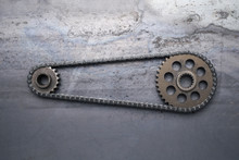Two Rusty Metal Gears Linked Together On A Grungy Background With A Drive Chain.