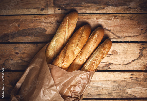 Valokuvatapetti Four baguette bread loaves in paper bag on wooden background