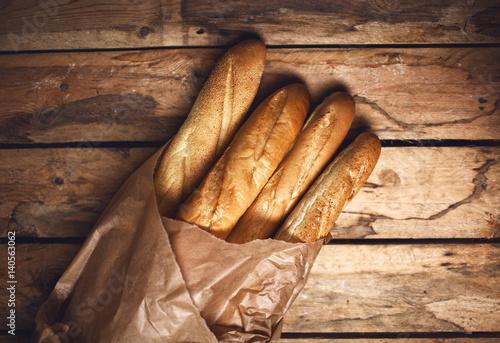 Fotografie, Obraz  Four baguette bread loaves in paper bag on wooden background