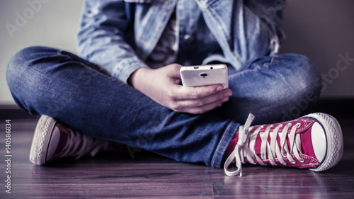 Fotografie, Obraz  Teenager uses a smartphone.