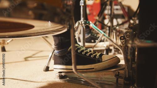 Plakat Próba zespołu rockowego w garażu - perkusista nosi trampki poruszające pedałem basu