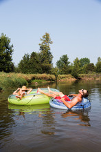 Couple Tubing Down The River In The Summer