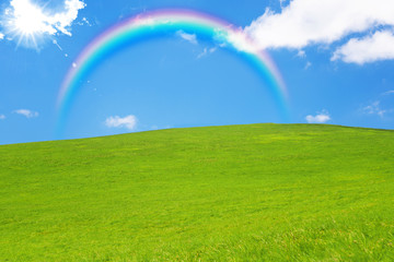 idyllic landscape of green heels, blue sky and rainbow