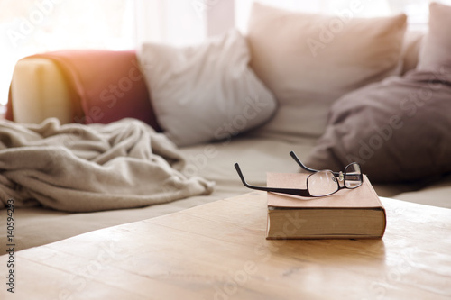 Obraz book with eyeglasses on table in front of couch - fototapety do salonu