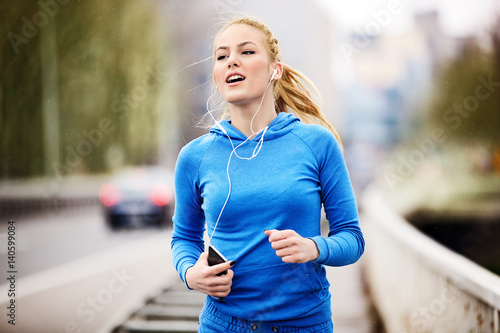 Woman jogging on bridge