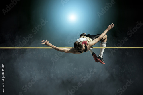 Athlete in action of high jump. Wallpaper Mural