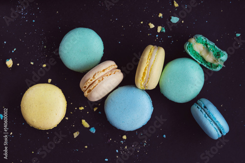 Foto op Plexiglas Macarons Macaroons on dark background, colorful french cookies macarons. The broken macarons with crumbs