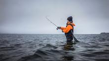 Angler In Wathose Mit Spinnrute Und Kescher Beim Wurf Mit Köder Im Winter Im Kalten Meer An Der Küste Bei Wolken
