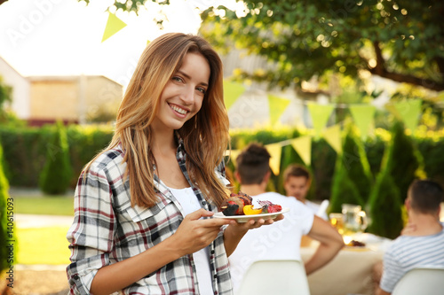 Pretty young woman holding plate with grilled meat and vegetables