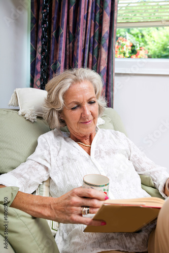 Foto op Canvas Kruidenierswinkel Senior woman with coffee cup reading book while relaxing on armchair at home