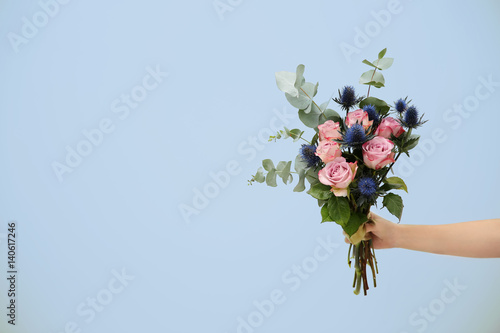 Photo Female hand holding beautiful bouquet on light background