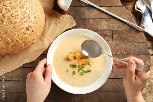 Foto auf Gartenposter Gewürze 2 Female hands and delicious cream soup on table