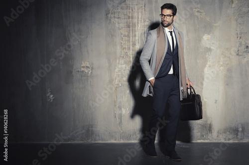 Fotografie, Obraz  Businessman in suit standing in shadowy studio