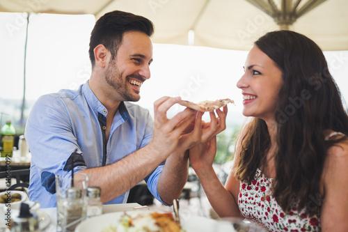 Fototapeta Couple sharing a slice of pizza outdoor obraz na płótnie
