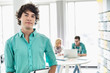 Portrait of confident businessman with colleagues working in background at creative office