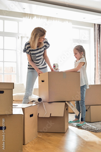 Fotografie, Obraz  Mother and daughter packing cardboard boxes at home