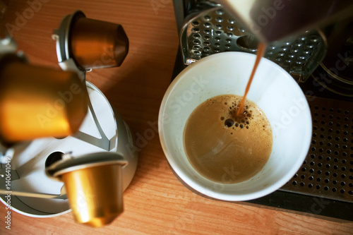 Fototapeta  Morning cup of fragrant coffee from coffee machine on the wooden background with