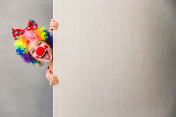 Funny kid clown playing indoor