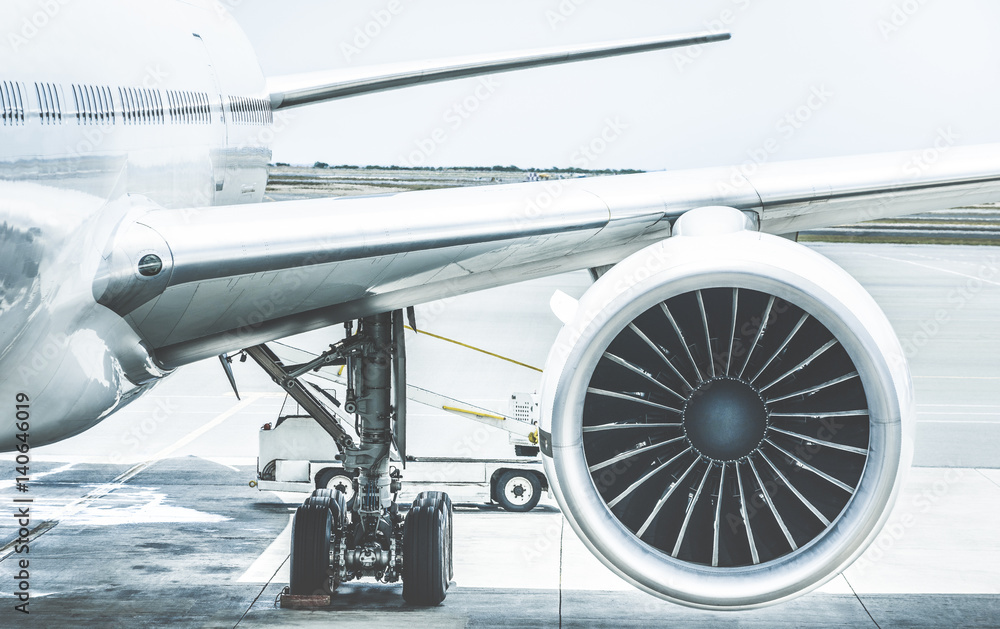 Fototapety, obrazy: Detail of airplane engine wing at terminal gate before takeoff - Wanderlust travel concept around the world with air plane at international airport - Retro contrast filter with light blue color tones
