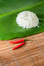 Fresh Cooked Heap Of Jasmine White Rice On Banana Leaf With Two Red Chili Peppers